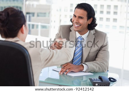 Manager shaking the hand of a female applicant in his office - stock photo