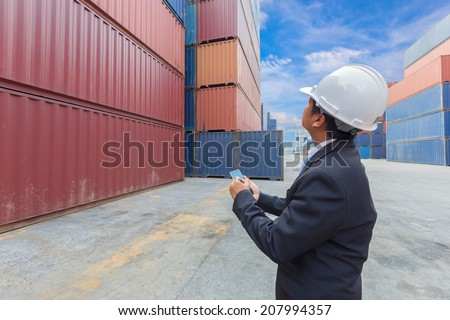 manager shipping company middle aged worker working at container depot with tablet on hand - stock photo