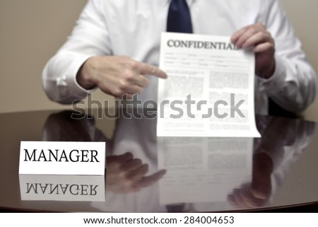 Manager sitting at desk holding Confidential document for deal  - stock photo