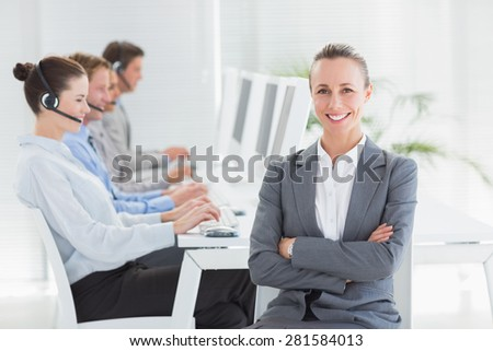 Manager smiling at camera with her staff behind in call center - stock photo