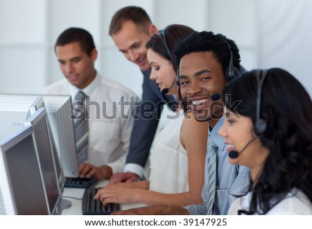 Manager talking to his multi-ethnic business team in a call center - stock photo