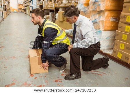 Manager training worker for health and safety measure in a large warehouse - stock photo