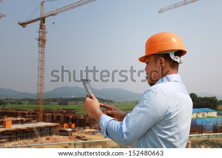 Manager using digital tablet on construction site - stock photo