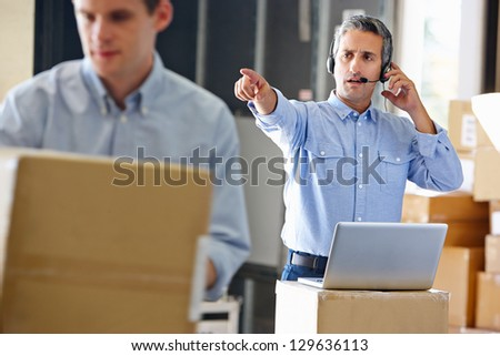 Manager Using Headset In Distribution Warehouse - stock photo
