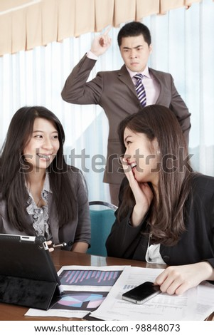 Manager watching his subordinate employees not working with anger - stock photo
