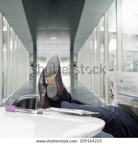 manager with feet on desk reading newspaper - stock photo