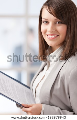 Manager with pad on the glass wall background with people - stock photo