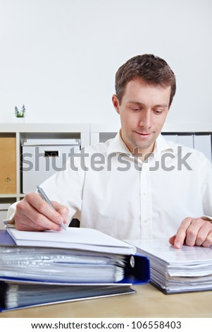 Manager working on files at his desk in his office - stock photo