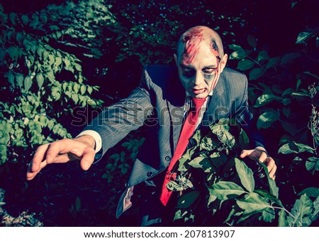 Manager zombie walking dead outdoors. Dark lighting. Color was changed to emphasize the atmosphere of horror. - stock photo