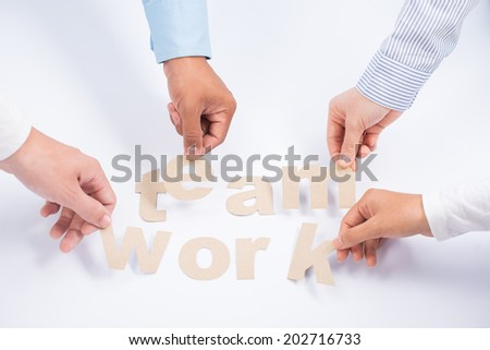Managers making the word teamwork out of paper letters - stock photo