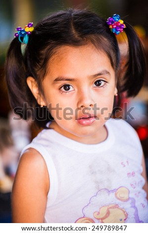 MANAGUA, NICARAGUA - JAN 6, 2012: Unidentified Nicaraguan little girl with pigtail. 69% of Nicaranguan people belong to the Mestizo ethnic group - stock photo