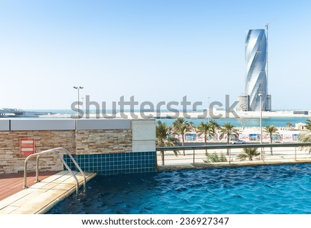 Manama, Bahrain - November 21, 2014: Swimming pool and United Tower under construction on the horizon in Manama city, Capital of Bahrain Kingdom - stock photo
