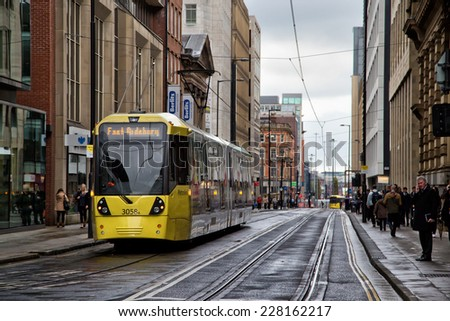 MANCHESTER,ENGLAND- OCTOBER 8,2014: A tram on the Metrolink light rail system makes its way down Mosley Street - stock photo