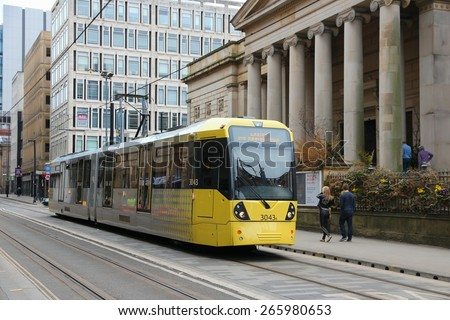 MANCHESTER, UK - APRIL 21, 2013: People ride Manchester tram in Manchester, UK. Manchester Metrolink serves 21 million rides annually (2011). - stock photo