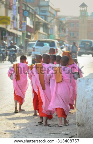 MANDALAY, MYANMAR - FEB 15, 2015. Buddhist nuns walking along a street for morning arms at Mandalay, Myanmar. They are wearing parasols. - stock photo