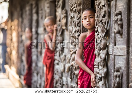 MANDALAY,MYANMAR- FEB 18 : Young monks standing and looking at Shwenandaw Monastery is built in the traditional Burmese architectural style on February 18,2015 in Mandalay,Myanmar. - stock photo