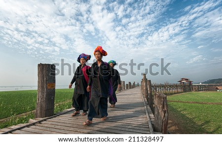 MANDALAY, MYANMAR - JAN 19, 2014: Unidentified Burmese women in traditional clothes visiting U Bein bridge and local Buddhist temple. Domestic tourism is important part of life for people of Myanmar - stock photo