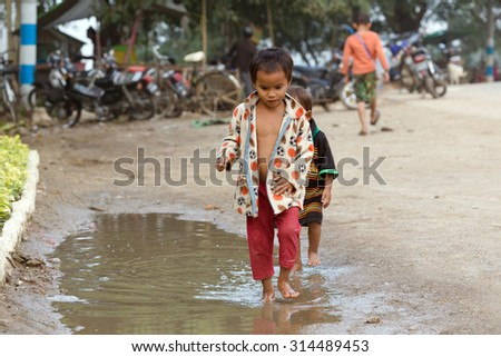 MANDALAY,MYANMAR,JANUARY 19, 2015 : A little boy is playing with his friend in the street, walking in a rain puddle in a slum area of Mandalay, Myanmar (Burma). - stock photo
