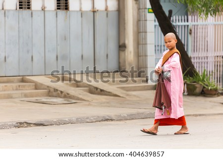 MANDALAY,MYANMAR,JANUARY 17, 2015: A young Buddhist nuns is walking in the streets of Mandalay, Myanmar (Burma). - stock photo