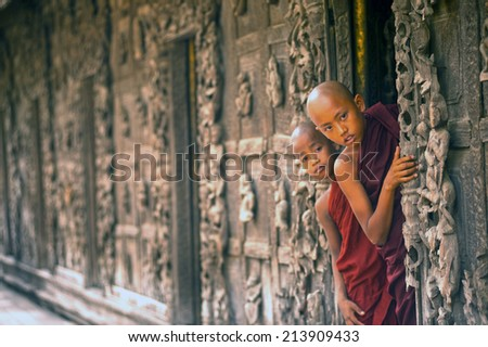 MANDALAY,MYANMAR-JUNE 28 : Young Novice monks standing and looking at Shwenandaw Monastery is built in the traditional Burmese architectural style on June 28,2014 in Mandalay,Myanmar.  - stock photo