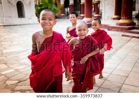 MANDALAY, MYANMAR-MAY 1 : Unidentified young Buddhism novice front temple at Hsinbyume pagoda temple onMAY 1, 2013 in Mandalay, Myanmar - stock photo