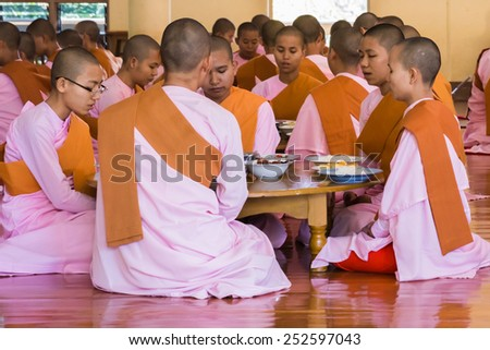 MANDALAY, MYANMAR - NOVEMBER 23, 2014:  many unidentified Buddhist nuns pray in their nunnery before the meal - stock photo