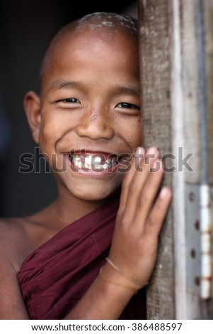 MANDALAY - MYANMAR - NOVEMBER 26, 2015: Unidentified smiling young Buddhist novice in a traditional Buddhist monastery on November 26, 2015 in Mandalay, Myanmar - stock photo