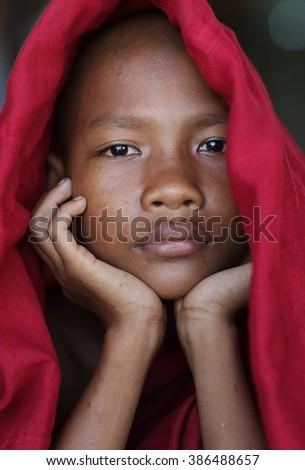 MANDALAY - MYANMAR - NOVEMBER 9, 2015: Unidentified young Burmese Buddhist novice in a monastic school on November 9, 2015 in Mandalay, Myanmar. - stock photo