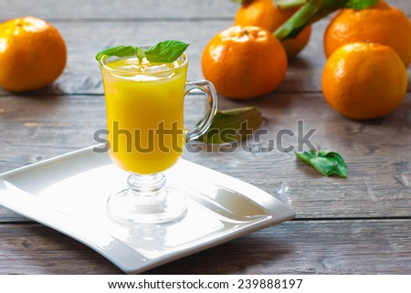 Mandarin  juice with leaf mint and ice cube on wooden background, selective focus - stock photo