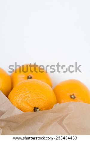 Mandarins out of the paper bag closeup isolated - stock photo