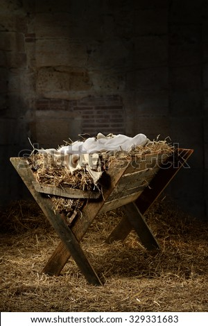 Manger filled with hay in stable with baby soft cloths on top - stock photo