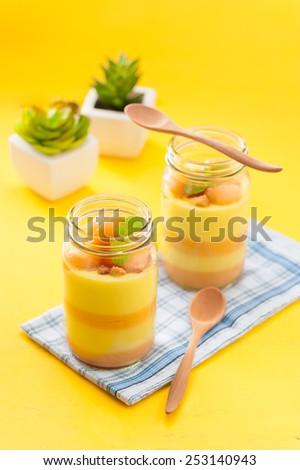 Mango and cantaloupe pudding in glass bottle - stock photo