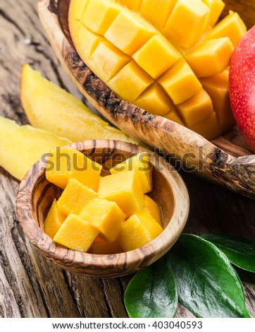 Mango fruit and mango cubes on the wooden table. - stock photo