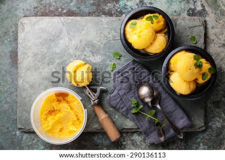 Mango ice cream sorbet with mint leaves in black bowls, Spoon for ice cream and plastic container on stone slate background - stock photo