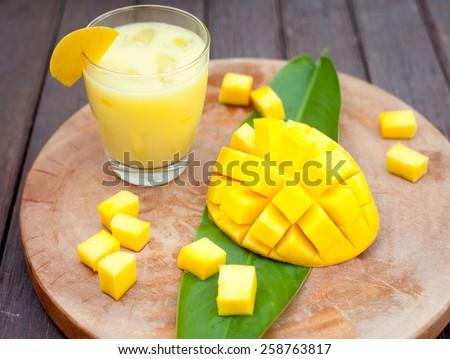 Mango juice, smoothie and mango fruit on a wooden background - stock photo