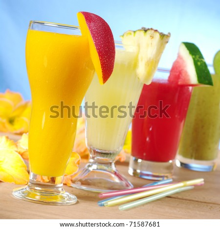 Mango, pineapple, watermelon and kiwi smoothie with drinking straws on wood (Selective Focus, Focus on the mango smoothie in the front) - stock photo
