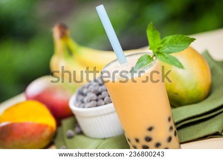 Mango smoothie bubble tea with fruit and tapioca pearls in the garden - stock photo
