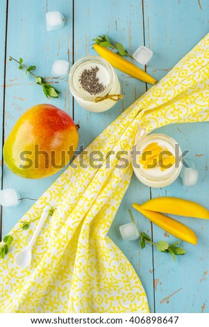 Mango with yogurt and chia seeds on a blue wooden background. Decorated with ice cubes and mint - stock photo