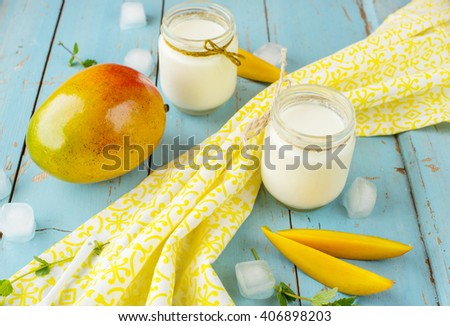 Mango with yogurt on a blue wooden background. Decorated with ice cubes and mint - stock photo