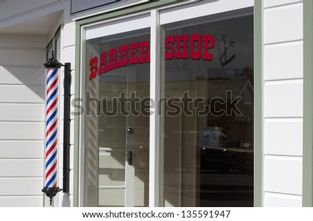 MANGONUI - APRIL 17:New barber shop window and pole on April 17 in Mangonui, NZ.Barbering is one of the oldest profession in the world dated back 6000 years ago in ancient Egypt. - stock photo