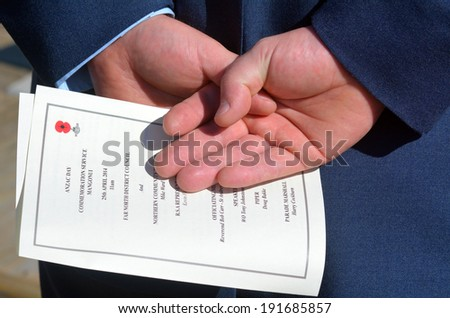 MANGONUI, NEW ZEALAND - APRIL 25 2014:New Zealand Army officer hands holds  ANZAC order of service during a National War Memorial Anzac Day in New Zealand. - stock photo