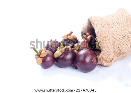 Mangosteen and cross section showing the thick purple skin and white flesh of the queen of friuts.  - stock photo