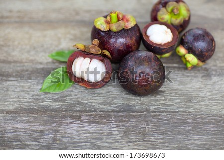 Mangosteens fruits and cross sections on wooden table - stock photo