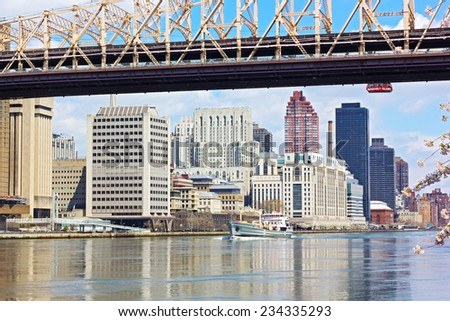Manhattan and East River with a ship passing by during cherry blossom. Beautiful spring morning on Roosevelt Island, New York. - stock photo