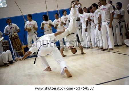 MANHATTAN BEACH, CA - SEPTEMBER 13: Mestres spar in the roda (circle) at the International Capoeira Festival.  Mestre Cabeca (R) kicks from an inverted position. Manhattan Beach, CA on Sept. 13, 2009. - stock photo