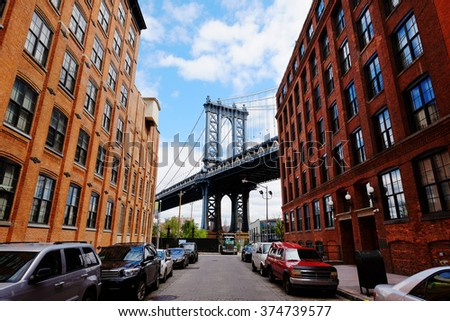 Manhattan bridge seen from a brick buildings in Brooklyn street in perspective, New York, USA - stock photo
