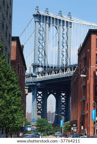 Manhattan Bridge Viewed from Brooklyn with the Empire State Building Visible Within Its Arch - stock photo