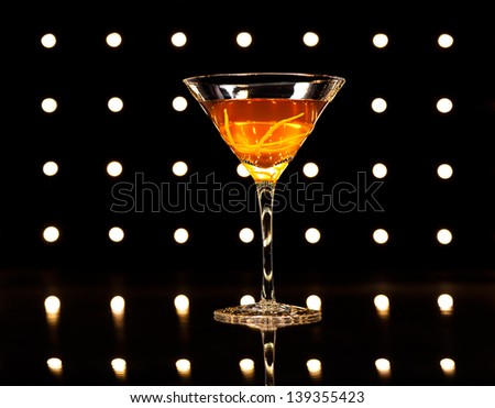 Manhattan cocktail in front of disco lights - stock photo