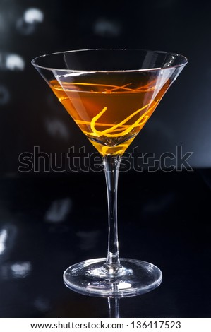 Manhattan cocktail over black and bright sparkles - stock photo