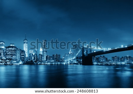 Manhattan Downtown urban view with Brooklyn bridge at night - stock photo